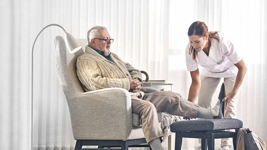 Health care professional helping an elderly man